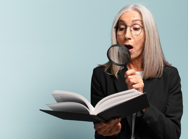 Senior mooie vrouw met een boek en een vergrootglas. zoek concept