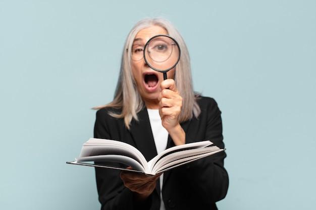 Senior mooie vrouw met een boek en een vergrootglas. zoekconcept