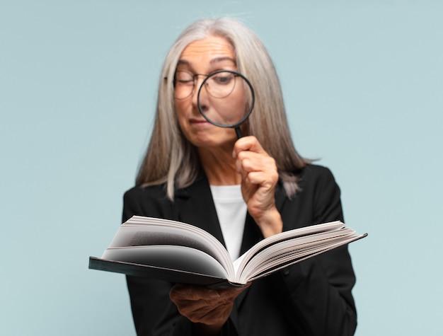 Senior mooie vrouw met een boek en een vergrootglas.