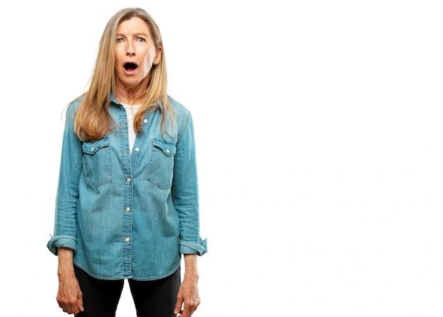 Senior mooie vrouw met een verbaasde, verbaasde uitdrukking en mond wijd open in shock.