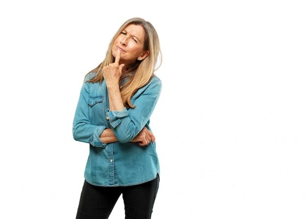 Senior mooie vrouw met een verwarde en doordachte look, zijwaarts op zoek, denken en af