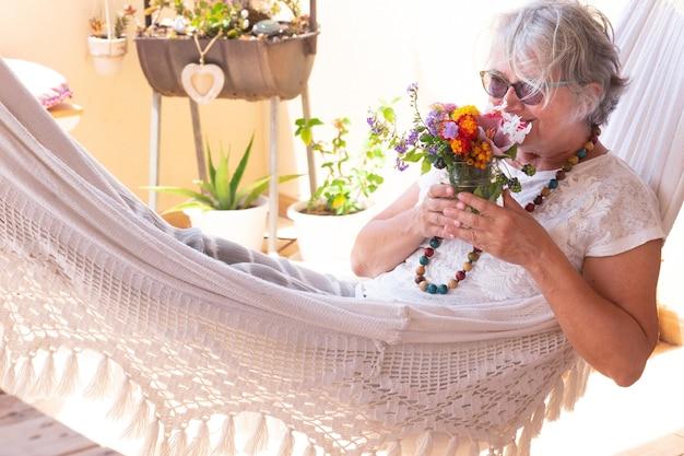 Senior mooie vrouw met grijs haar liggend op een witte hangmat en snuift een boeket bloemen. ontspannend moment buiten op het terras. positieve vibes