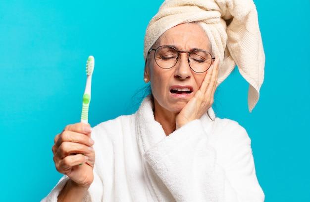 Senior mooie vrouw na douche badjas dragen en met een tandenborstel
