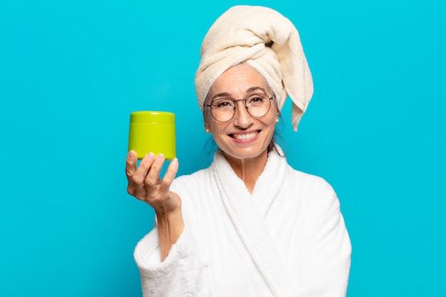Senior mooie vrouw na douche badjas dragen. gezichtsreiniging of doucheproducten concept