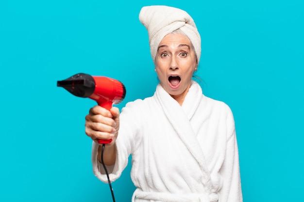 Senior mooie vrouw na douche badjas dragen. haardroger concept