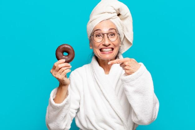Senior mooie vrouw na het douchen en het dragen van badjas en ontbijten met een donut