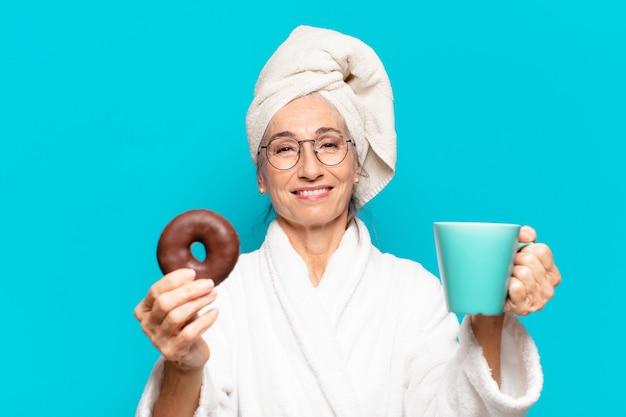 Senior mooie vrouw na het douchen en het dragen van badjas en ontbijten met koffie en donut