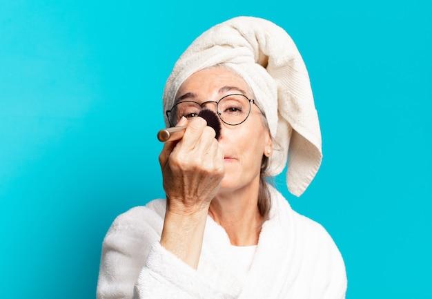 Senior mooie vrouw na het douchen make-up en het dragen van badjasrob