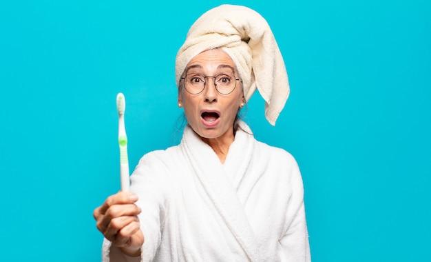 Senior mooie vrouw na het douchen met een badjas en een tandenborstel