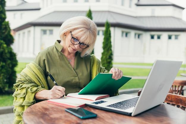 Senior mooie zakelijke vrouw zittend op een stoel en het maken van aantekeningen in een notitieblok met een telefoon