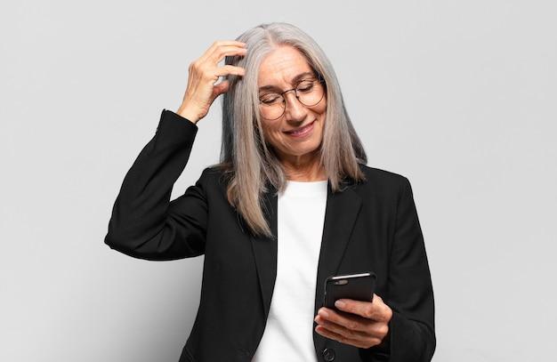 Senior mooie zakenvrouw met een slimme telefoon