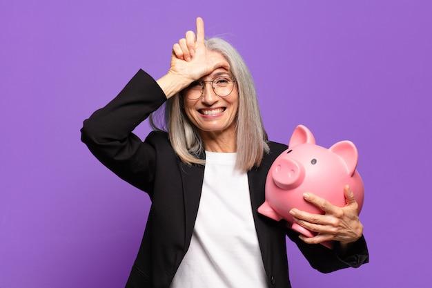Senior mooie zakenvrouw met een spaarvarken