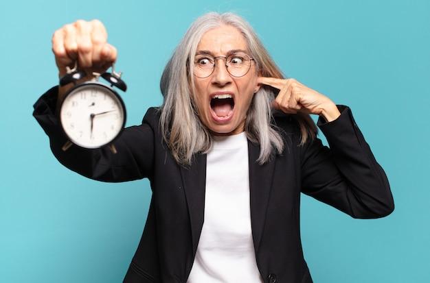 Senior mooie zakenvrouw met een wekker. tijd concept