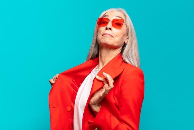 Senior mooie zakenvrouw met rode zonnebril en jas