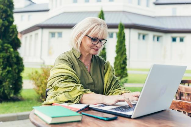 Senior mooie zakenvrouw zittend op een stoel en het maken van aantekeningen in een notitieblok, met een telefoon en laptop in de tuin