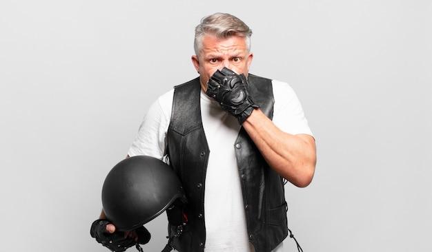 Senior motorrijder bedekt mond met handen met een geschokte, verbaasde uitdrukking, houdt een geheim of zegt oeps