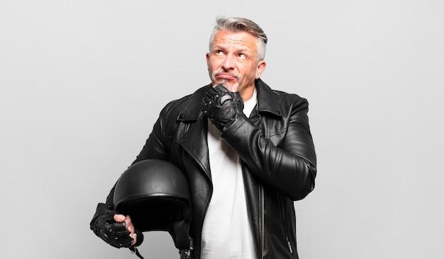 Senior motorrijder denken, zich twijfelachtig en verward voelen, met verschillende opties, zich afvragend welke beslissing te nemen