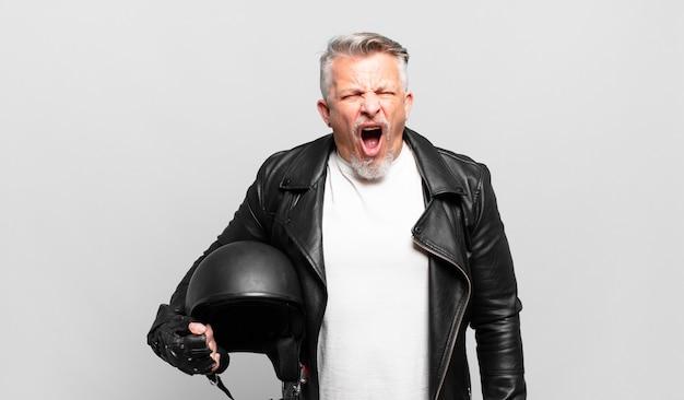 Senior motorrijder die agressief schreeuwt, erg boos, gefrustreerd, verontwaardigd of geïrriteerd kijkt, nee schreeuwt