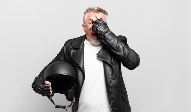 Senior motorrijder die geschokt, bang of doodsbang kijkt, het gezicht bedekt met de hand en tussen de vingers gluurt
