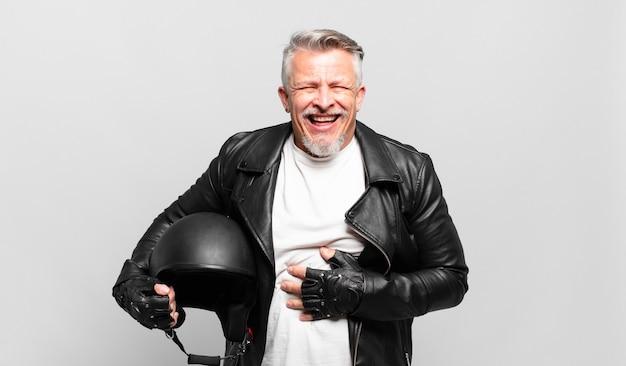 Senior motorrijder die hardop lacht om een hilarische grap, zich gelukkig en opgewekt voelt, plezier heeft