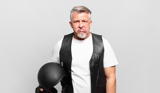 Senior motorrijder die verbaasd en verward kijkt, lip bijt met een nerveus gebaar, niet wetend het antwoord op het probleem