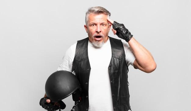 Senior motorrijder die verrast, met open mond, geschokt kijkt en een nieuwe gedachte, idee of concept realiseert
