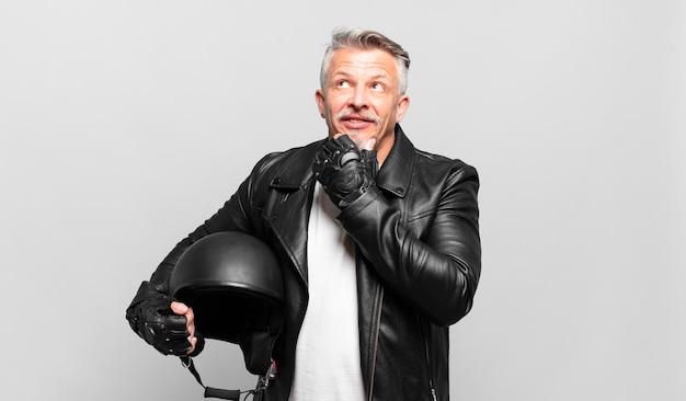 Senior motorrijder die vrolijk lacht en dagdroomt of twijfelt, opzij kijkend