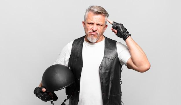 Senior motorrijder die zich verward en verbaasd voelt en laat zien dat je gek, gek of gek bent