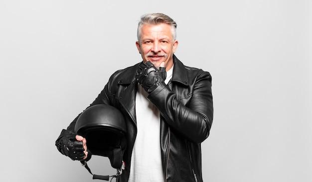 Senior motorrijder glimlachend met een gelukkige, zelfverzekerde uitdrukking met de hand op de kin, zich afvragend en opzij kijkend