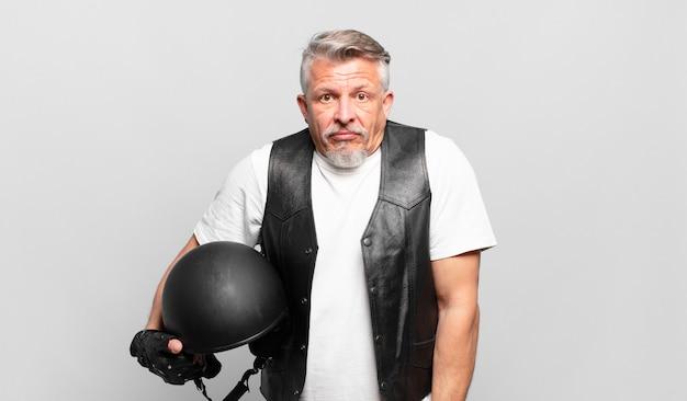 Senior motorrijder haalt zijn schouders op, voelt zich verward en onzeker, twijfelt met gekruiste armen en kijkt verbaasd