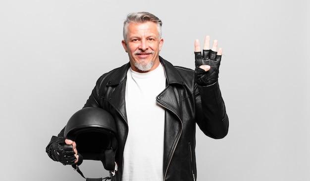 Senior motorrijder lacht en ziet er vriendelijk uit, toont nummer vier of vierde met de hand naar voren, aftellend