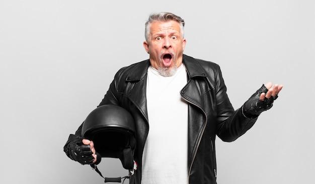 Senior motorrijder met open mond en verbaasd, geschokt en verbaasd met een ongelooflijke verrassing