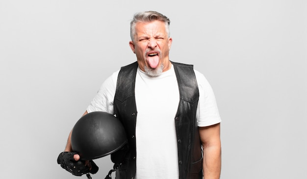 Senior motorrijder met vrolijke, zorgeloze, rebelse houding, grappen maken en tong uitsteken, plezier maken