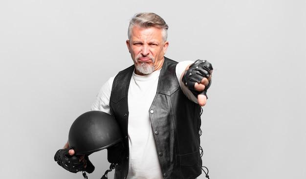 Senior motorrijder voelt zich boos, boos, geïrriteerd, teleurgesteld of ontevreden, duimen naar beneden met een serieuze blik