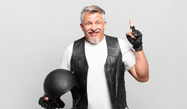 Senior motorrijder voelt zich een gelukkig en opgewonden genie na het realiseren van een idee, vrolijk vinger opsteken, eureka!