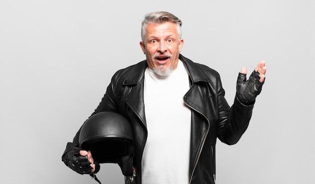 Senior motorrijder voelt zich gelukkig, verrast en opgewekt, glimlacht met een positieve houding, realiseert een oplossing of idee