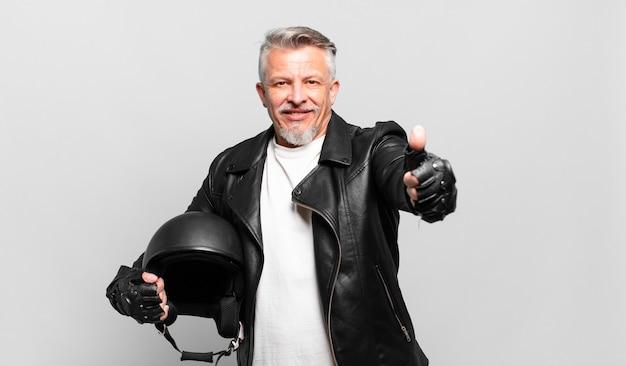 Senior motorrijder voelt zich trots, zorgeloos, zelfverzekerd en gelukkig, positief glimlachend met duimen omhoog