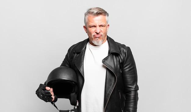 Senior motorrijder voelt zich verdrietig, overstuur of boos en kijkt opzij met een negatieve houding, fronsend in onenigheid