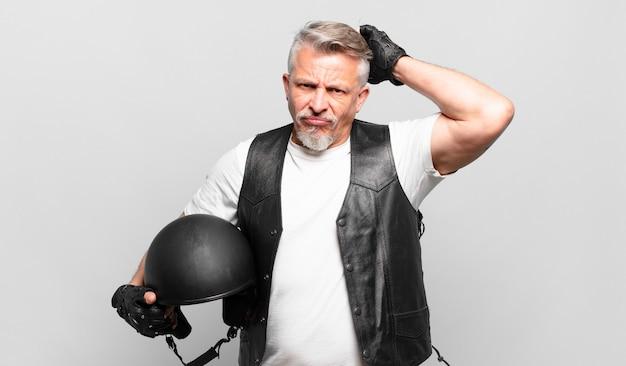 Senior motorrijder voelt zich verward en verward, krabt aan zijn hoofd en kijkt opzij