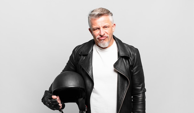 Senior motorrijder voelt zich verward en verward, met een stomme, verbijsterde uitdrukking die naar iets onverwachts kijkt