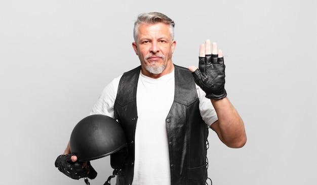 Senior motorrijder ziet er serieus, streng, ontevreden en boos uit en toont een open palm die een stopgebaar maakt