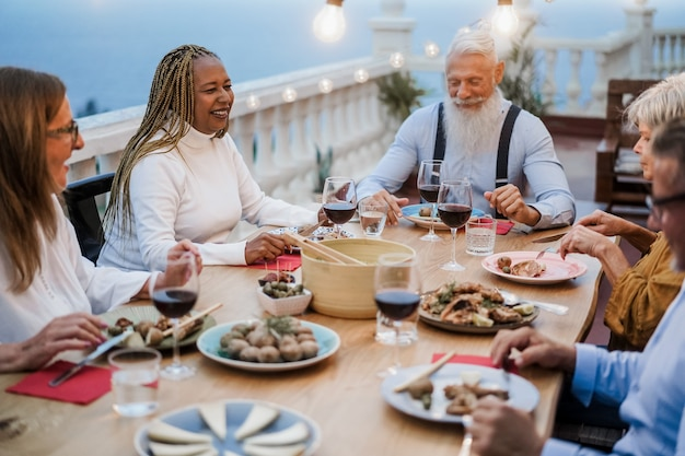 Senior multiraciale mensen die plezier hebben tijdens het diner op het terras - focus op het gezicht van de afrikaanse vrouw