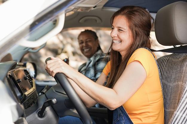 Senior multiraciale vrouwen op een roadtrip met camper - volwassen vrienden zingen in minibusje tijdens het rijden voor vakantie in de natuur