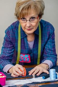 Senior naaister poseren kijkend naar camera met tafel met naaimaterialen op de achtergrond