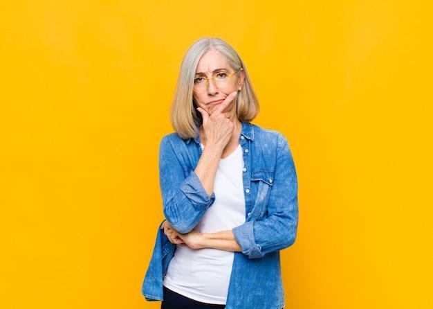 Senior of middelbare leeftijd mooie vrouw die ernstig, attent en wantrouwend kijkt, met één arm gekruist en hand op kin, wegingsopties