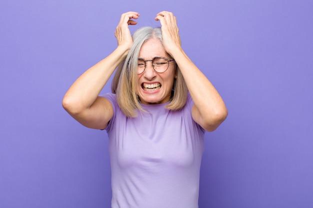 Senior of middelbare leeftijd mooie vrouw die zich gestrest en angstig, depressief en gefrustreerd voelt met hoofdpijn, waarbij beide handen tegen het hoofd worden geheven