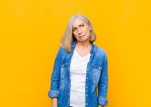 Senior of middelbare leeftijd mooie vrouw die zich verdrietig, boos of boos voelt en opzij kijkt met een negatieve houding, fronsend van onenigheid