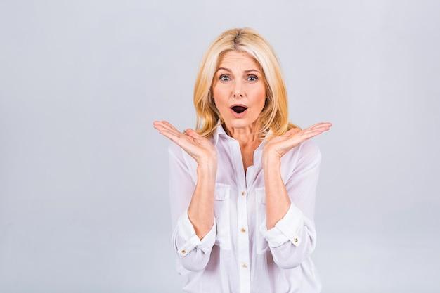 Senior of middelbare leeftijd mooie vrouw geschokt en opgewonden, lachen, verbaasd en blij vanwege een onverwachte verrassing geïsoleerd op witte achtergrond.
