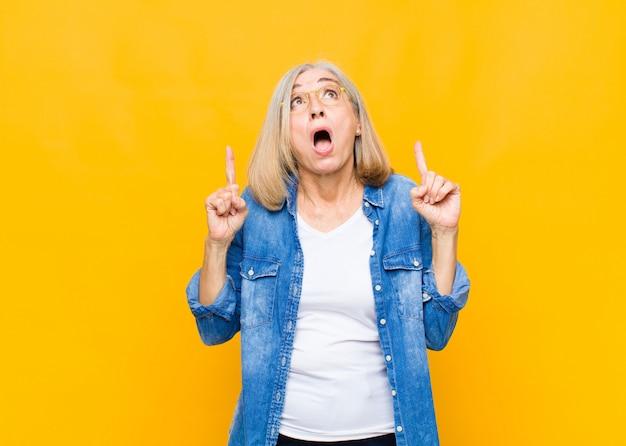 Senior of middelbare leeftijd mooie vrouw gevoel ontzag en open mond naar boven wijzend met een geschokte en verbaasde blik