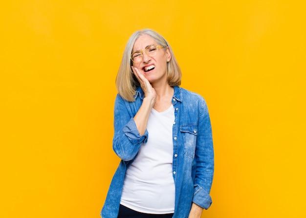 Senior of middelbare leeftijd mooie vrouw met wang en pijnlijke kiespijn, zich ziek, ellendig en ongelukkig voelen, op zoek naar een tandarts